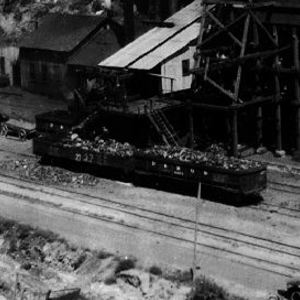 Click this thumbnail for a full view of Tipple and screening plant of Chesterfield Mining Company, from across the canyon,  Old washing  house  on right. Tracks from mine  are  higher  ones in  left center.  Ballard's prospect appears in upper right at shadow made by massive (Thompson's) sandstone ledge. Shows Palisade coal, Ballard coal, Thompson Canyon sandstone, Chesterfield coal zone,  Neslen member. Grand County, Utah. August 11, 1926. Published as plate 5-A in U.S. Geological Survey. Bulletin 852. 1926.